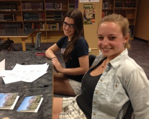 Seniors Callie Carlucci and Sarah Ellsworth write thank-you notes to Conference on World Affairs panelists in the Boulder High library during B lunch.  Both produced panels for the 2014 conference. (Photo by Jayden Simelda-Longe)